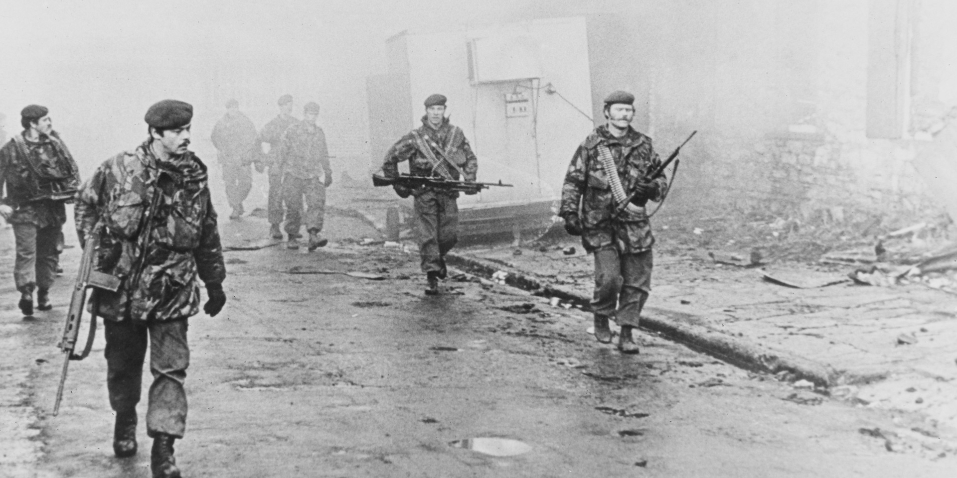 A view of a group of paras on foot patrol down a ruined street on the Falklands, 1982