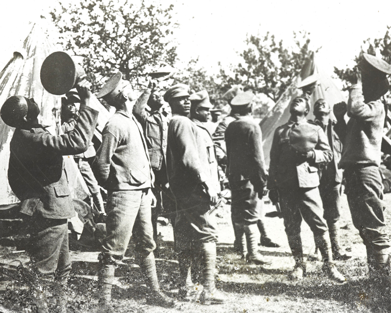 Members of the British West Indies Regiment observe aircraft above their camp near Amiens, 1918