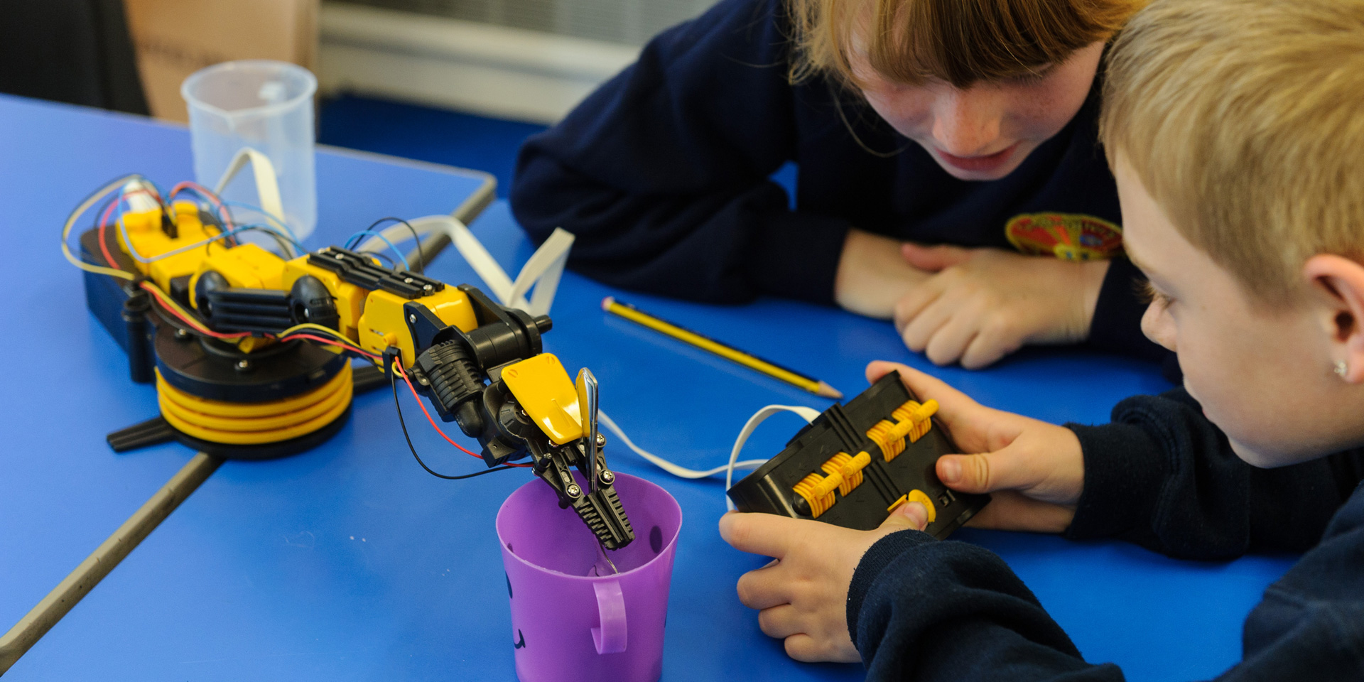 Students operate a robotic arm
