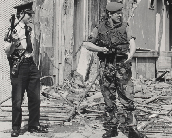 An RUC officer and Royal Military Policeman stand guard by a bombed building, 1979