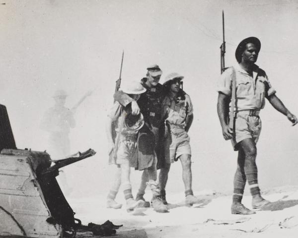 British troops help a wounded German prisoner, 1942