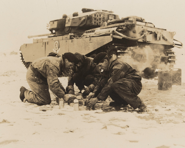 A tank crew from the 8th (King's Royal Irish) Hussars make a meal during their service on the Imjin front, 1951