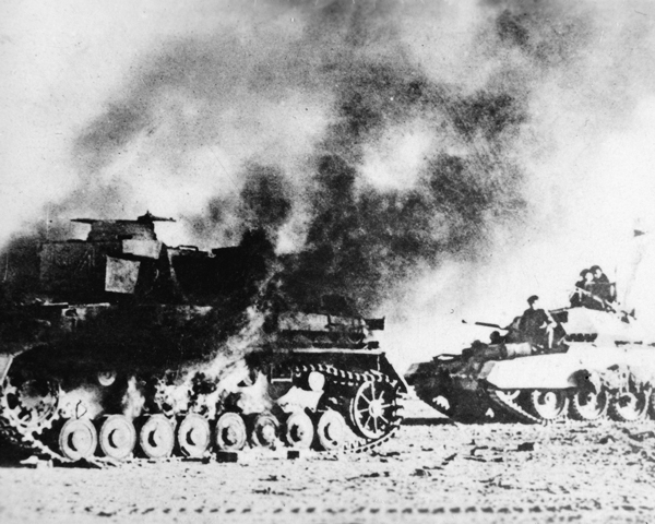 A British Crusader tank passes a burning German Panzer Mk IV, 1941
