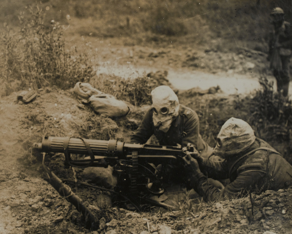 A Vickers machine gun team wearing gas masks, 1916