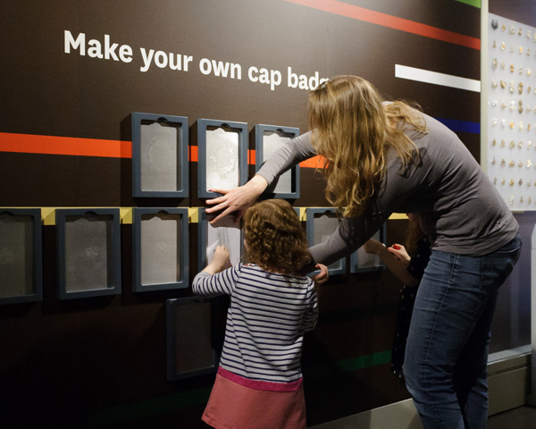 A family does cap badge rubbings in Army gallery