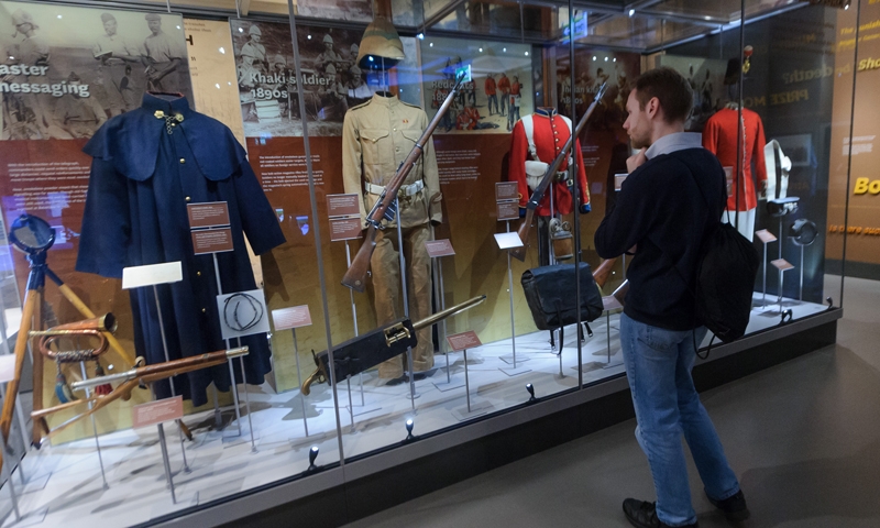 A visitor looks at a display case of uniform in Battle gallery