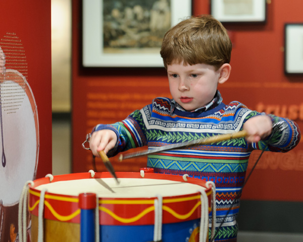 A child uses the interactive drum