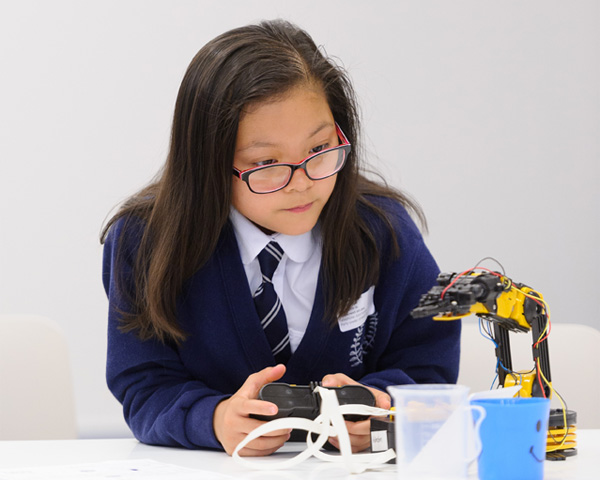 School girl carrying out a task using a robotic arm