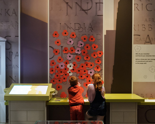 Two children interact with the poppy wall