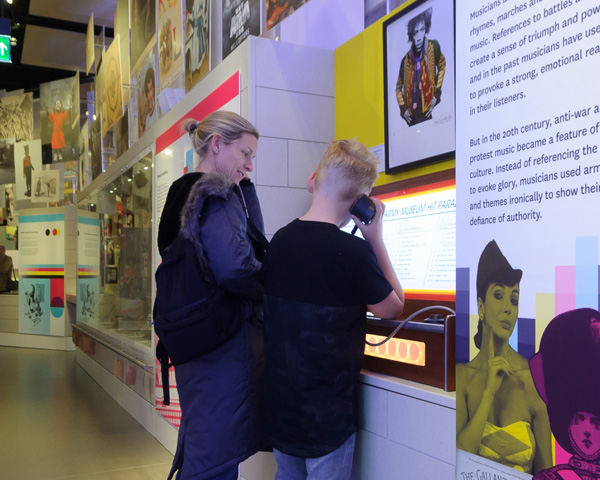 Family listening to army-inspired songs in Society gallery