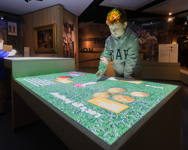 A visitor uses the interactive touch table