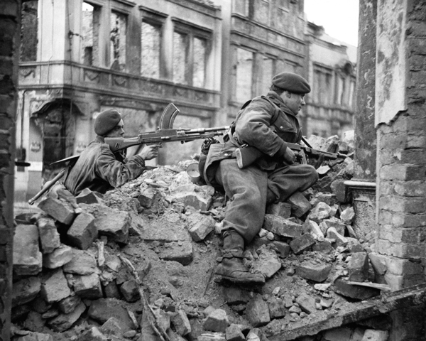 Members of No. 10 (Inter-Allied) Commando watch for snipers among the ruins of Osnabruck, 4 April 1945
