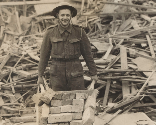 An Army Pioneer helps clear rubble, London, 1940