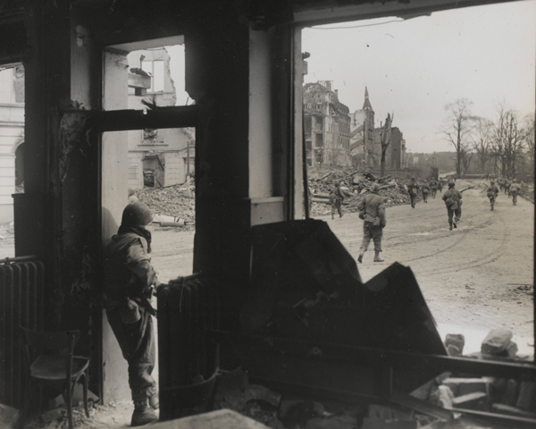 An American patrol advances towards the centre of a war-torn German town, 1945