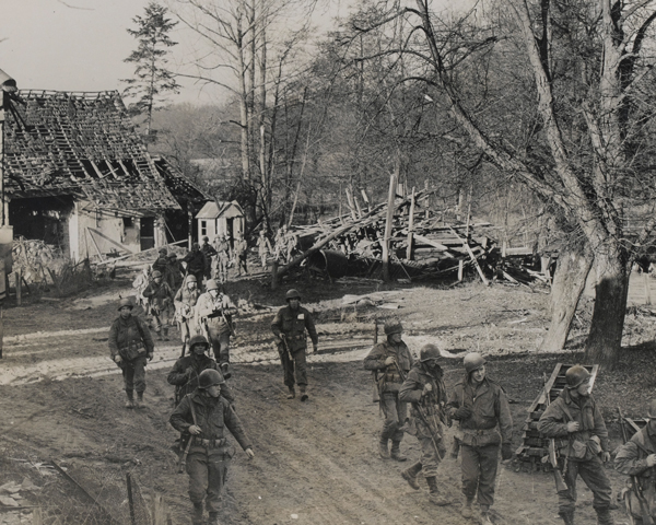 Soldiers of the US 7th Army move through a shell-torn village, 1944