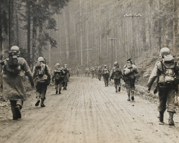 Infantry from the US 7th Army march through a forest, January 1945