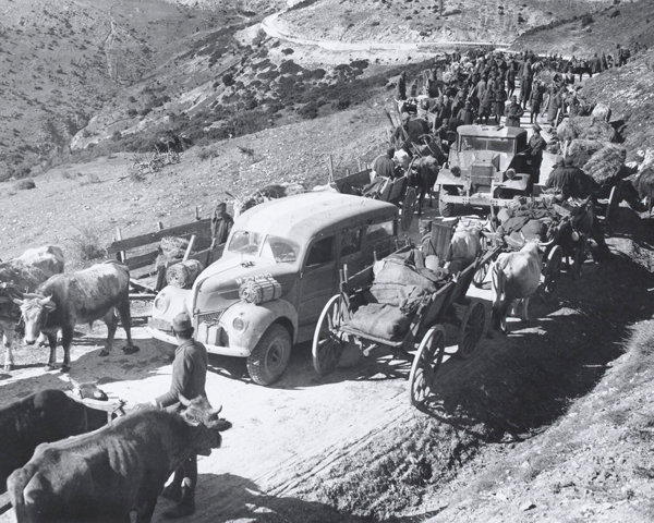 British vehicles pass through a Greek column, 1941