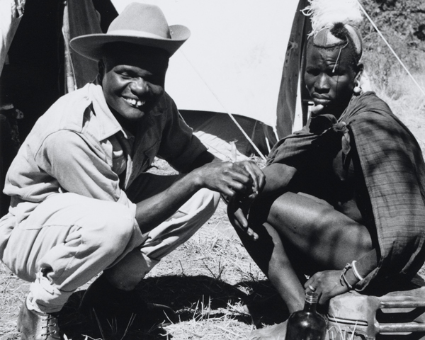 A medical orderly of the 4th King's African Rifles attends to a Kenyan villager, 1955