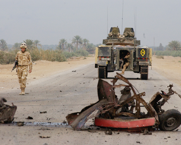 A British officer walks from his Warrior armoured vehicle to the scene of an insurgent car bomb, 2004