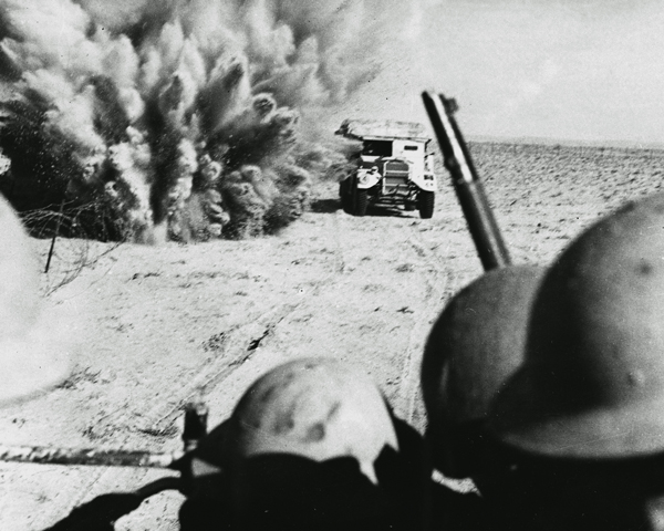 A mine explodes close to a British artillery tractor as it advances through minefields at El Alamein, 1942