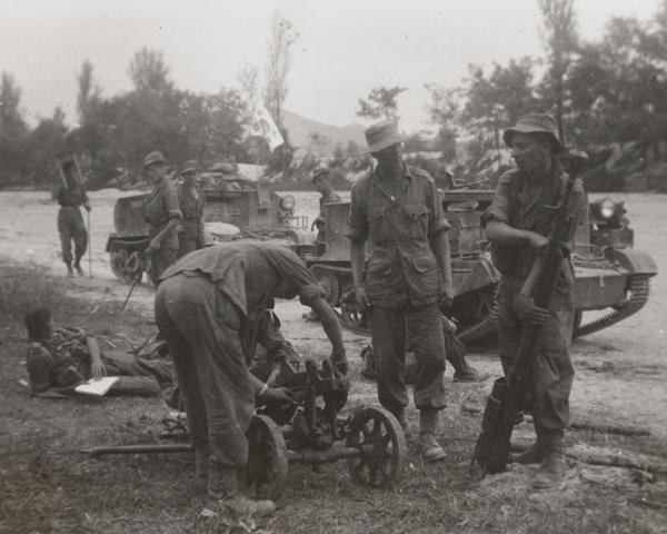 British troops examine a North Korean Maxim machine gun captured during their advance from the Pusan bridgehead in September 1950