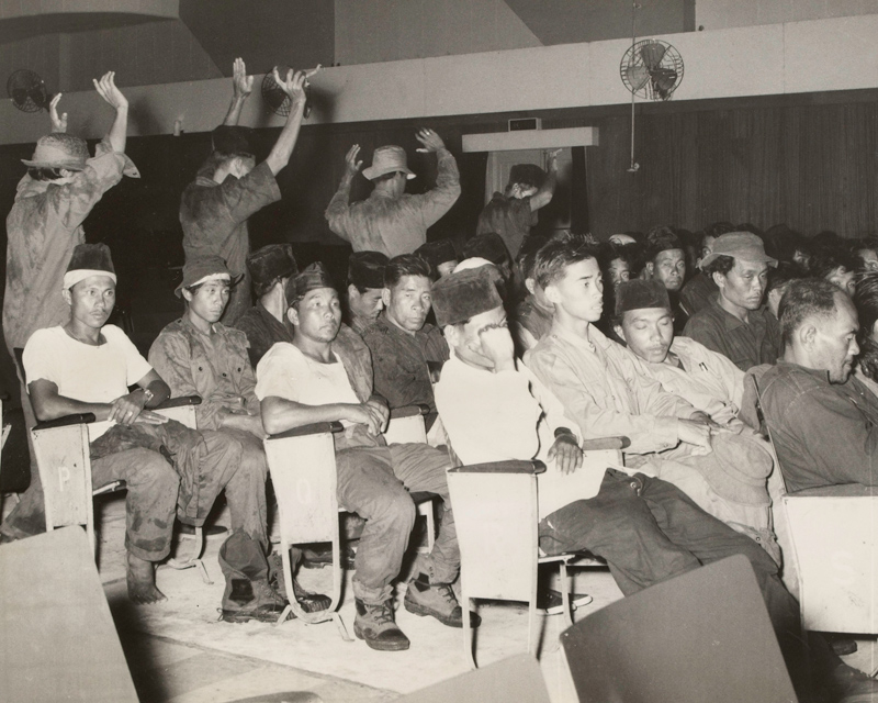 Rebel prisoners under Gurkha guard in a Brunei cinema, December 1962