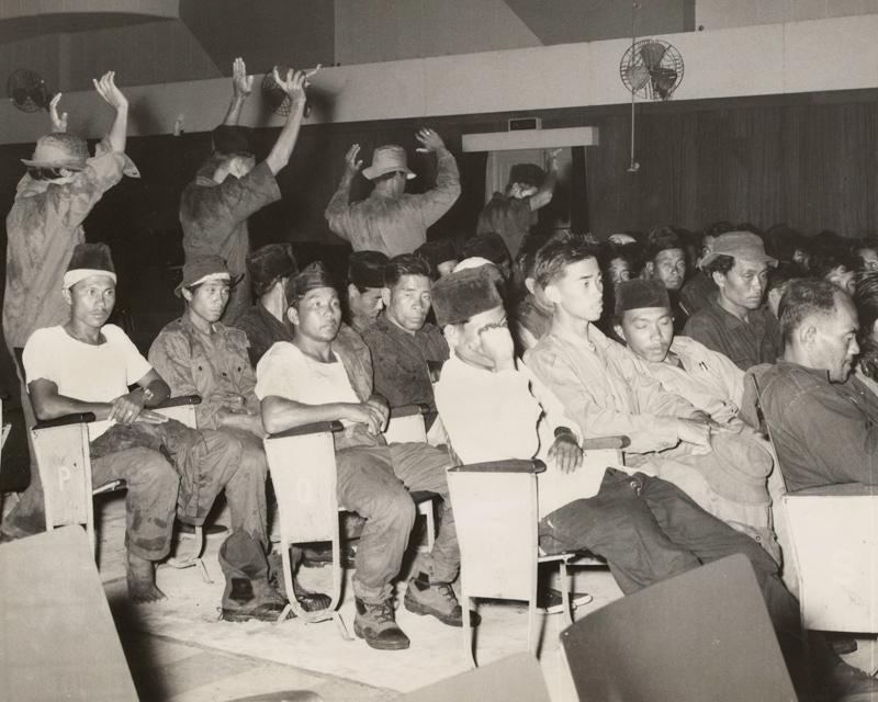 Rebel prisoners under Gurkha guard in a Brunei cinema, December 1962