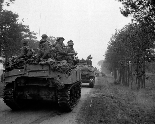 Infantry hitch a ride on a tank of 4th Armoured Brigade, September 1944