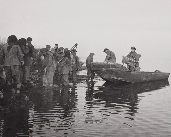 Men of 40 Royal Marine Commando unload a boat at Lake Comacchio, Italy, where they captured crossings vital to the main infantry advance, 11 April 1945