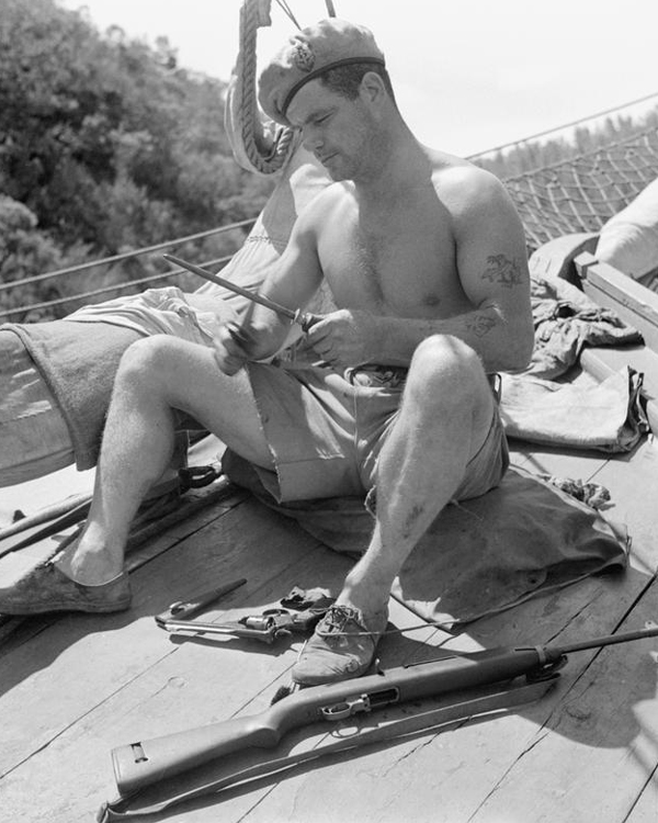 Corporal Aubrey, Special Boat Service, sharpens his fighting knife while preparing for a mission, 1945
