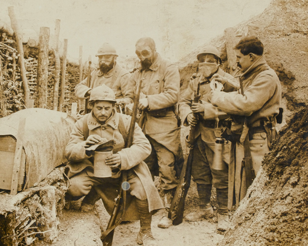 French troops don their gas masks while manning a trench, 1915