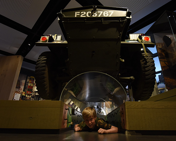 Child playing under dingo tank
