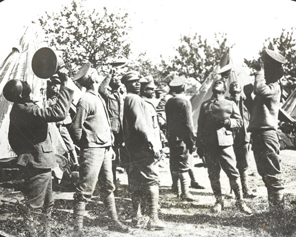 Members of the British West Indies Regiment observe aircraft above their camp on the Albert to Amiens Road, 1918