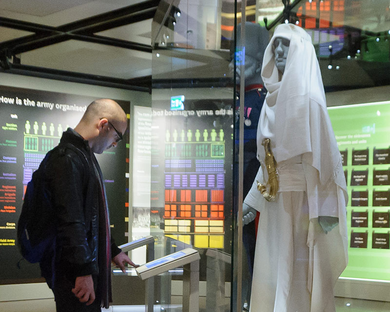 Visitor looking at Lawrence of Arabia robes and dagger