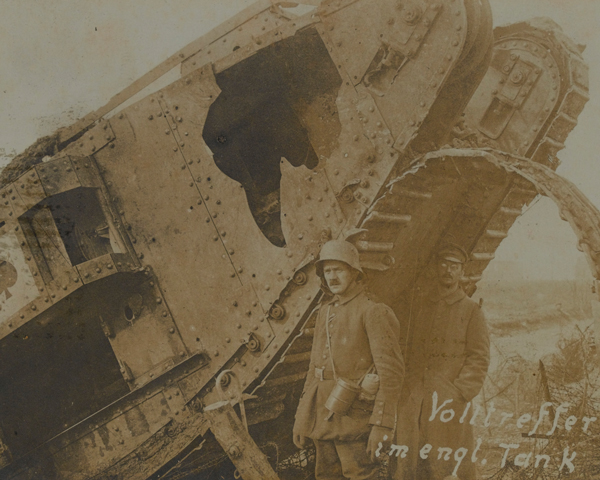 A German soldier next to a knocked-out British tank at Cambrai, 1917