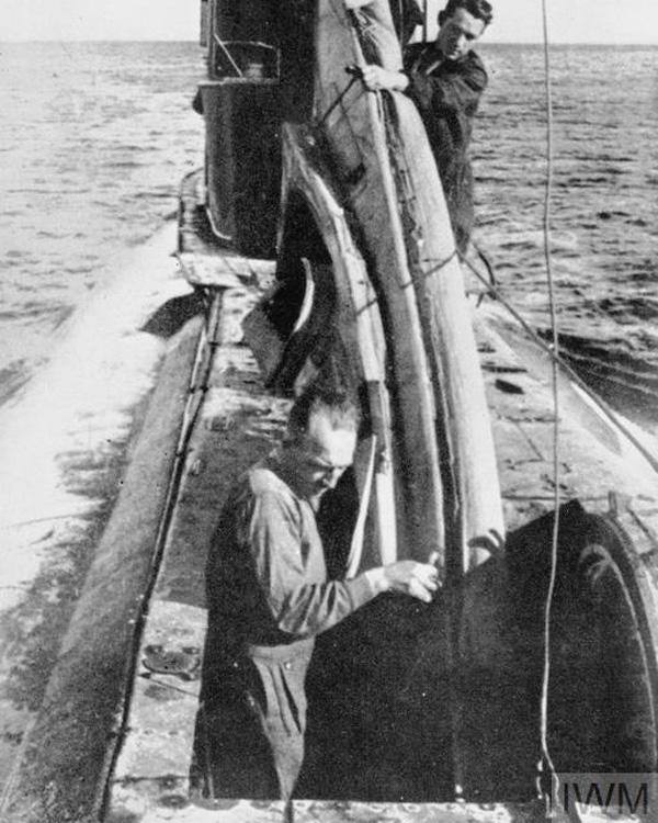 Robin Harbud and Sgt Cox manhandle their COPP canoethrough the forward hatch of a submarine