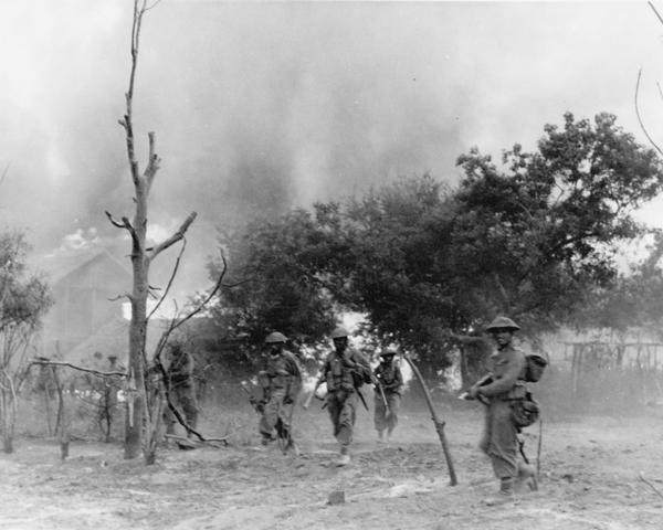 Indian infantry advance through a burning village, Burma, 1945