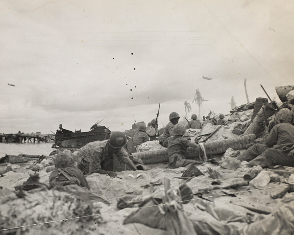 US Marines take cover on a beach as dive-bombers fly overhead, Okinawa, April 1945