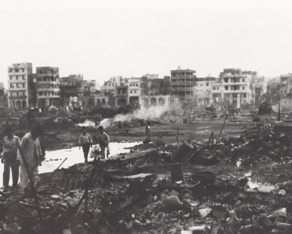 Egyptian civilians survey the burnt out ruins in Port Said, 1956