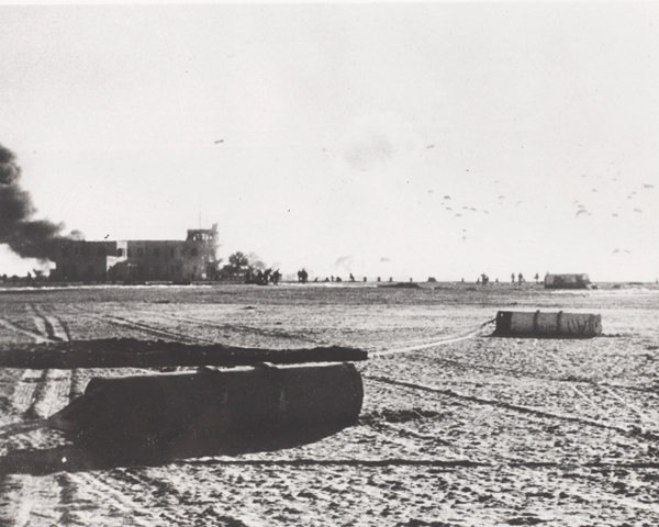 Equipment canisters litter El Gamil airfield as paratroopers land on the drop zone, 1956
