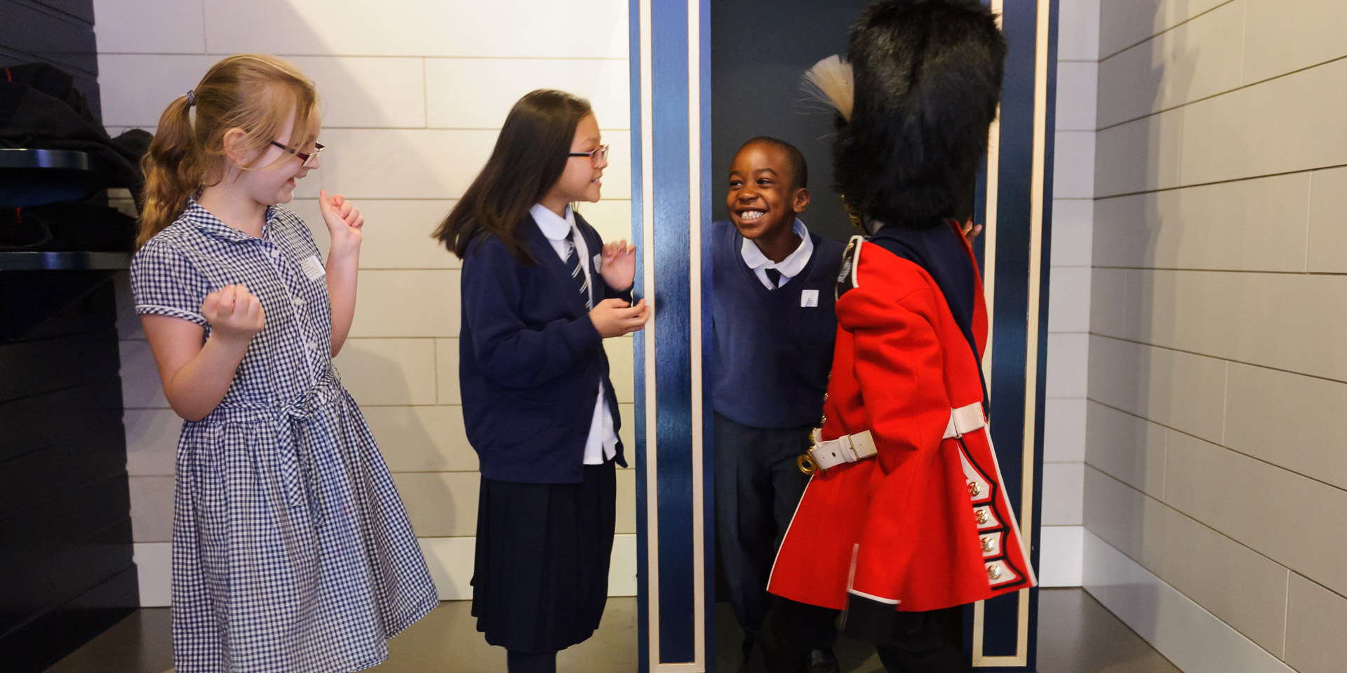 Kids trying on uniforms in Society gallery