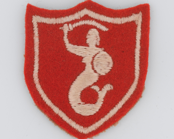 Sleeve badge worn by The Queen's Own Hussars, showing the crest of the city of Warsaw, c1958
