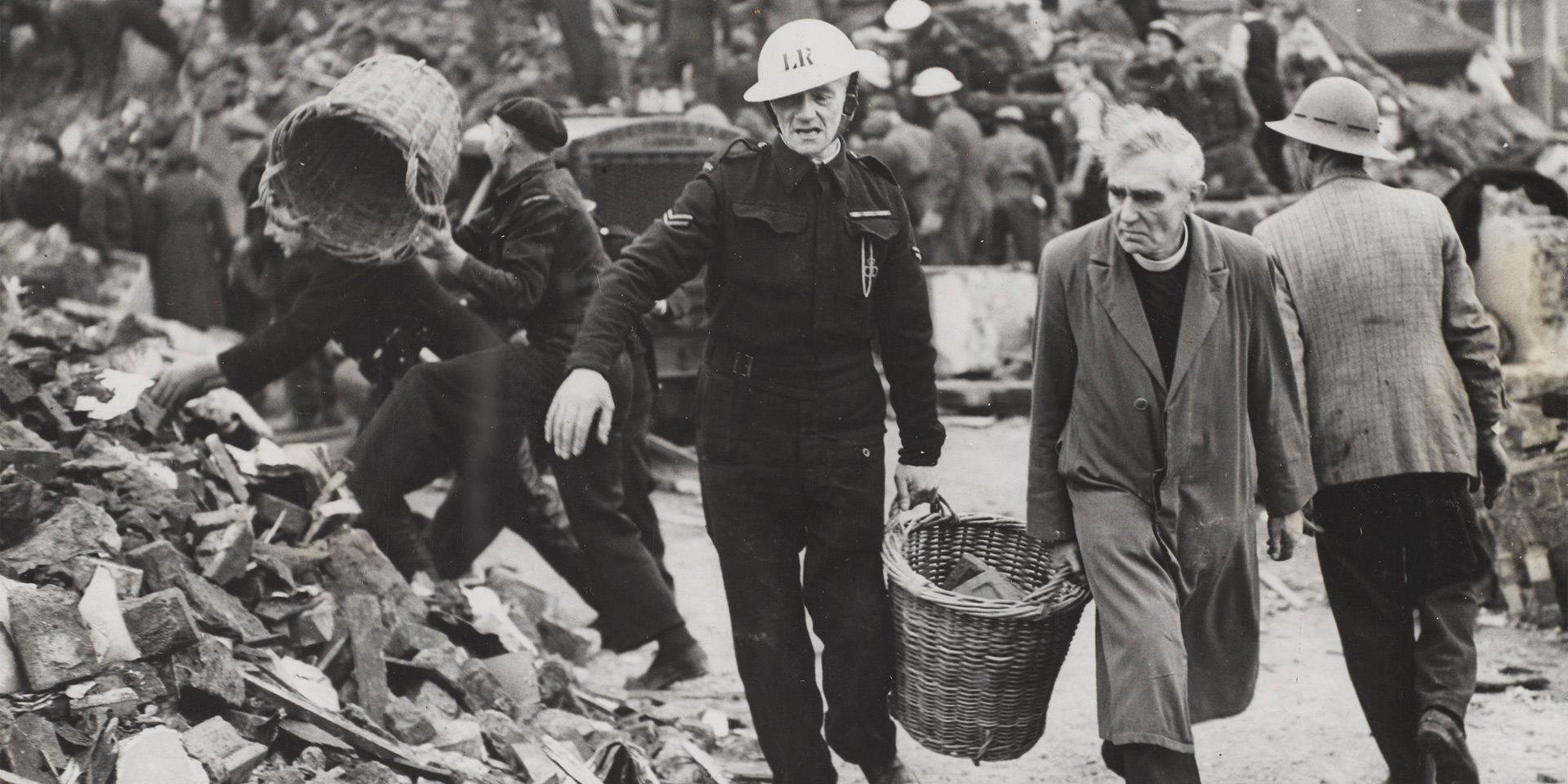 A clergyman and Civil Defence workers helping to clear the debris of a London school, 1940