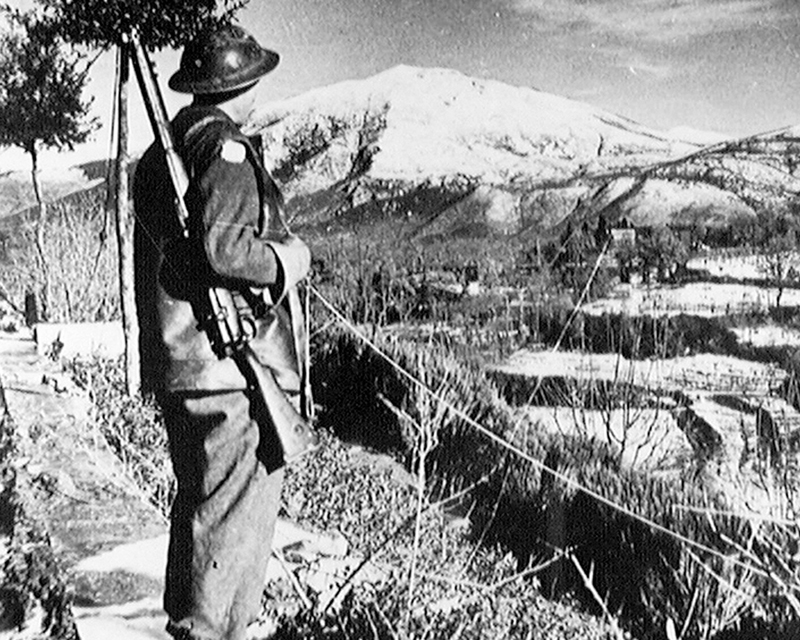 Driver CA Langford, Royal Army Service Corps, looks over the snow covered peaks of the American Fifth Army's front in Italy, 1944