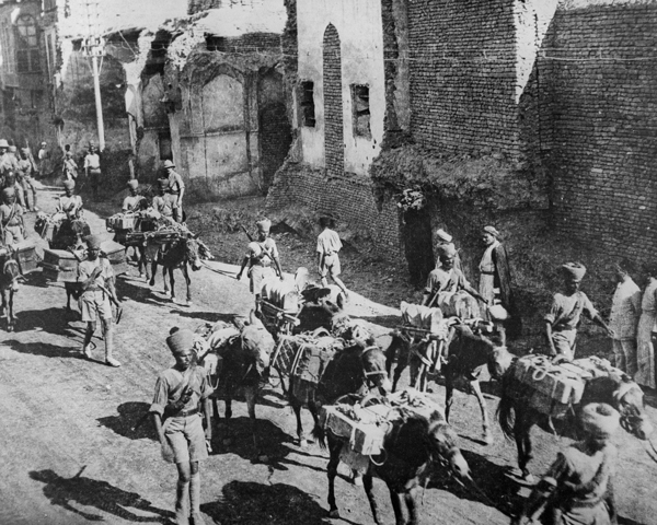 Indian soldiers march through Baghdad with donkeys loaded with supplies and ammunition, 1917