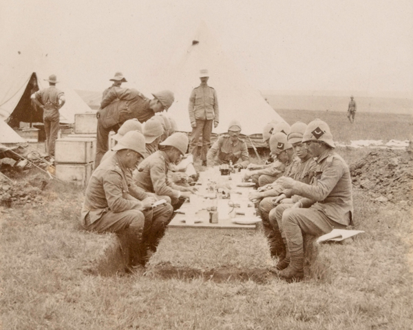 Officers of The Queen's Royal West Surrey Regiment eat lunch in the field, c1900