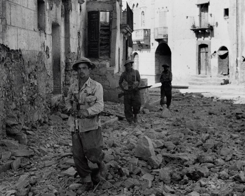 Members of the 6th Queen's Own Royal West Kent Regiment on patrol in Adrano, Sicily, 1943