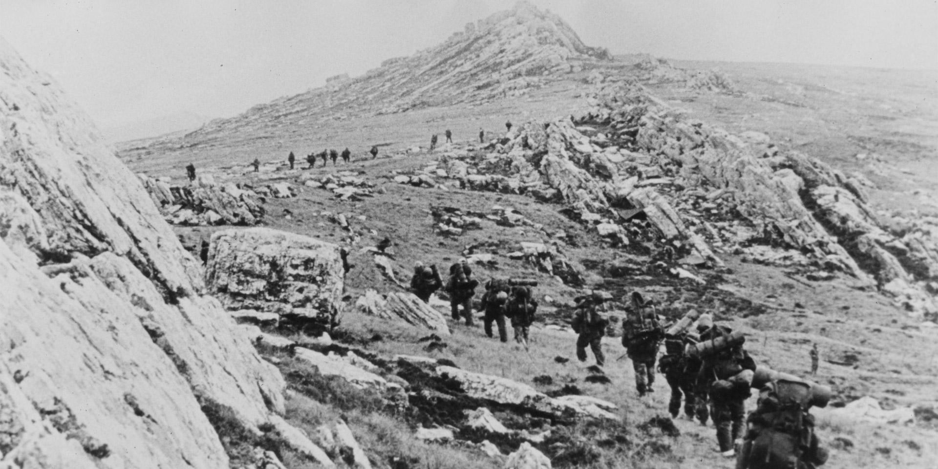 British troops march across the rocky Falklands terrain, 1982