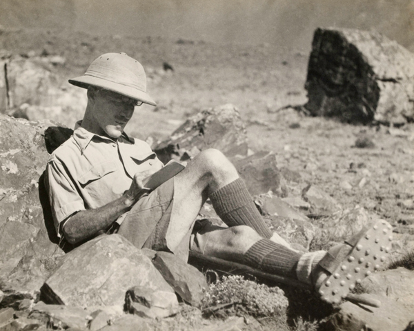 Colonel Guy Hamilton Russell filling in his game book while on a hunting expedition, 1930