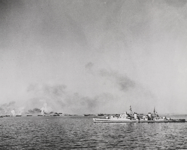 HMS 'Spartan' shells shore positions as landing craft approach, Anzio, 22 January 1944